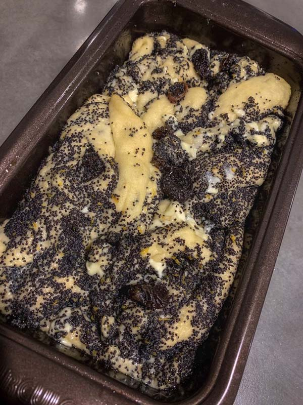 Babka dough mixed with poppy seeds and other ingredients inside a bread pan