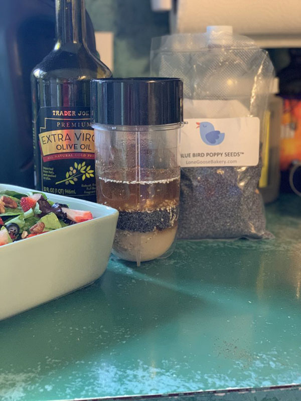 Poppy seeds, olive oil, and other salad dressings in a mixing container