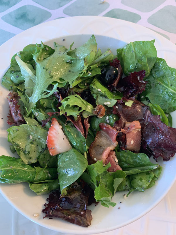 Green salad in a white bowl with cut strawberries and poppy seed dressing mixed in