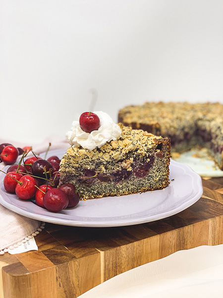 A slice of cake with whipped cream and a cherry on it