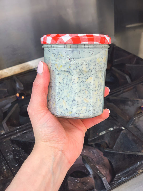 Left hand holding a lidded jar of overnight oats over a stove top
