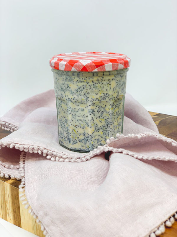 A jar filled with overnight oats with a red and white checker patterned lid