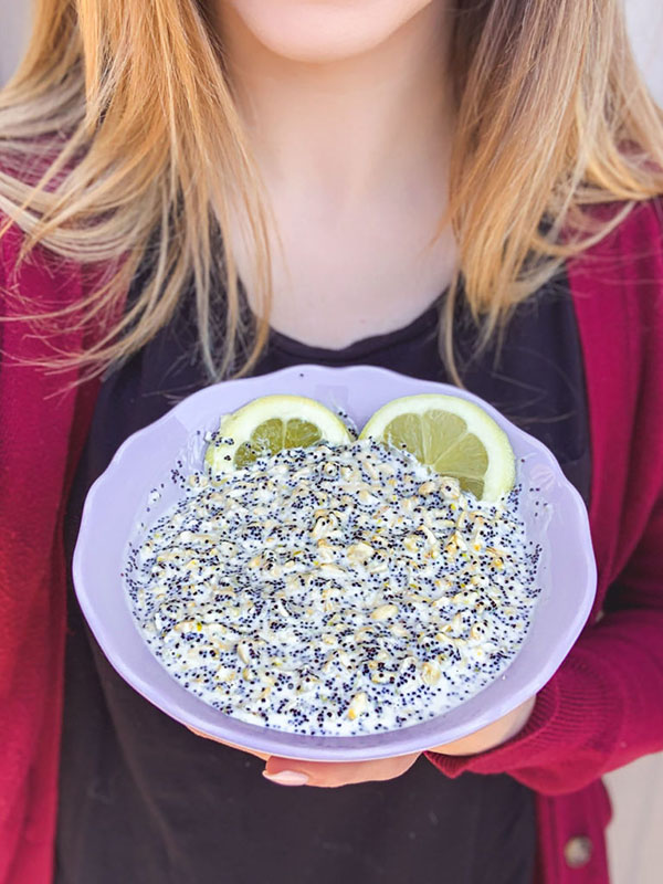 Woman with blonde hair holding a purple bowl of overnight oats