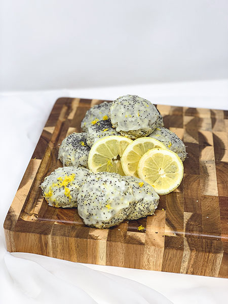 Cookies stacked on a cutting board with lemon slices on them