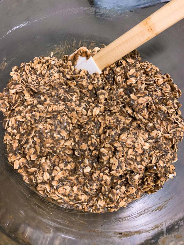 Oatmeal poppy seed cookie batter being mixed in a clear glass bowl