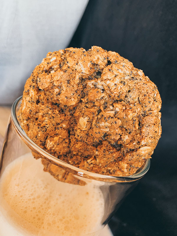 Large oatmeal cookie hanging loosely in the top of a glass of milk