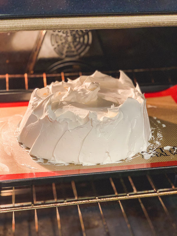 meringue covered cake on a baking sheet in the oven