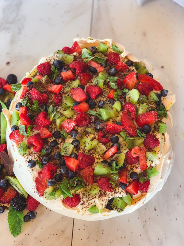 Meringue topped cake with an assortment of colorful fruits garnishing the top