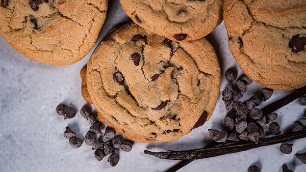 Chocolate chip cookies next to vanilla beans and chocolate chips