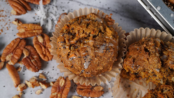 Close up of muffins with pecans and poppy seeds next to them