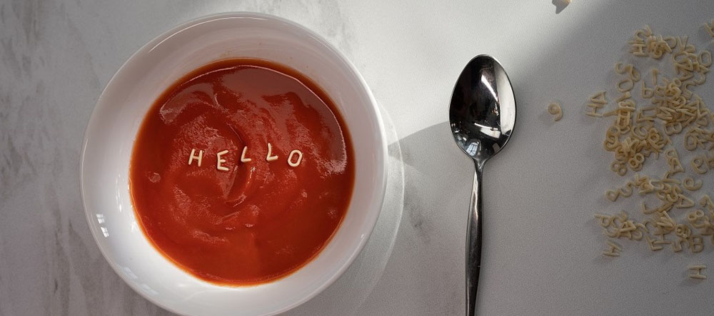 A bowl of sauce that says hello next to a spoon