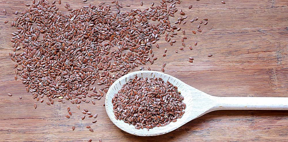 Flax seeds on a table next to a wooden spoon full of flax seeds