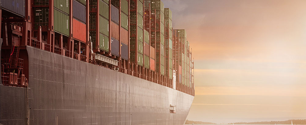 A cargo ship with lots of crates close to land