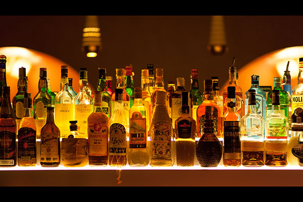 A bar with many different bottles on shelves