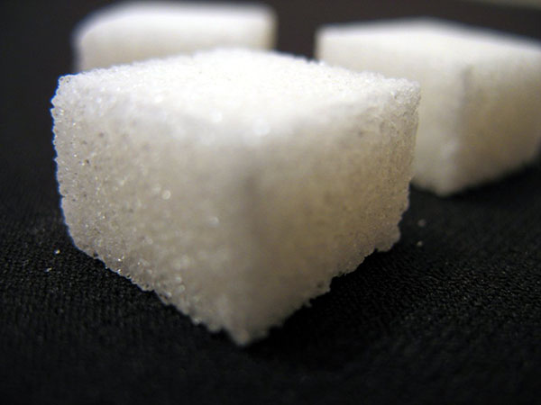 three sugar cubes sitting on a black table