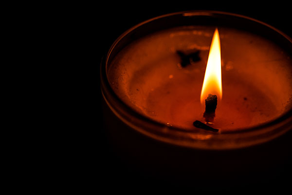 Lit candle in a dark room