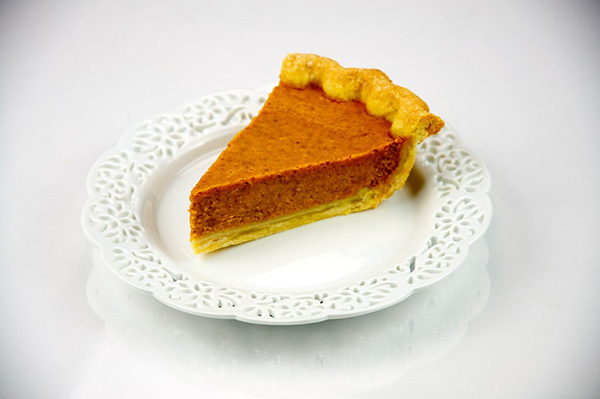 a single slice of pumpkin pie served on a saucer