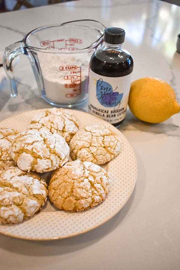 Lemon Goo Goo Cookies on a plate with pure vanilla extract next to it
